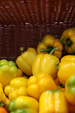 flavoring: Closeup seasoning fresh vitamin yellow colored bell sweet spicy flavoring peppers in half empty semi-vacant flat-bottom basket, vertical picture