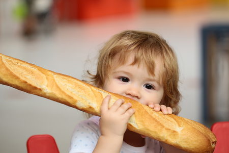 kid shopping: Closeup portrait of beautiful pretty cute hazel-eyed kid with shoulder-length blond wavy hair holding and biting French bread riding red and blue shopping trolley against grey background, horizontal
