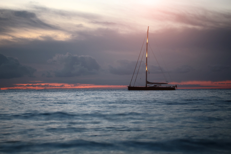 under view: Beautiful calm evening seascape with silhouette of yacht under bare poles floating in blue sea waves after red sunset in background on the horizon distant view, horizontal picture Stock Photo