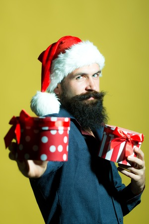 One handsome senior new year man with long black beard in shirt and red santa claus hat holding two wrapped present boxes in hands for christmas standing in studio on yellow background, vertical photo