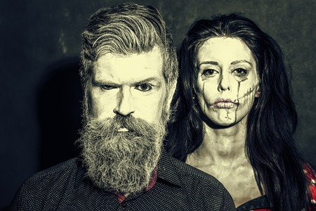 pranks: Closeup view of couple of painted halloween holy chrackters woman and man with long lush beard looking forward on studio wall sepia background, horizontal picture