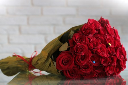birthday bouquet: Closeup of one big beautiful colorful soft aroma fresh wedding or birthday bouquet of many red rose flowers lying sunny day outdoor on natural background, horizontal picture