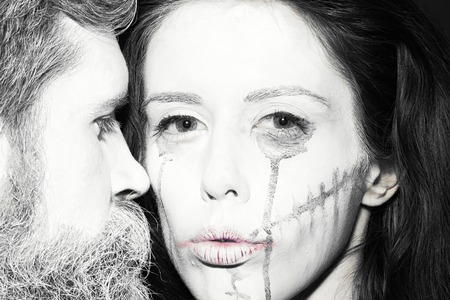 immortal: Closeup view of couple of painted halloween holy chrackters woman and man with long lush beard looking forward on studio wall background black and white, horizontal picture Stock Photo