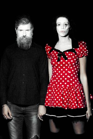 pranks: Full length view of couple of painted halloween holy chrackters woman in red dress and man with long lush beard looking forward on studio wall background black and white, vertical picture