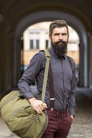 one young man: One handsome stylish young man with long black beard in blue shirt and purple trausers standing with travel bag outdoor in autumn street near arch, vertical picture