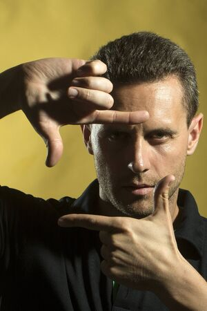 young unshaven: Portrait of one handsome young muscular sexual unshaven man in black t-shirt standing in studio holding hands in gesture near face looking forward on yellow background, vertical picture