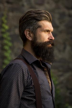 Close-up zijaanzicht van een knappe senior man met zwart haar en lange weelderige baard in het blauwe shirt en paars trausers staan buiten op stenen muur grijze achtergrond, verticale foto
