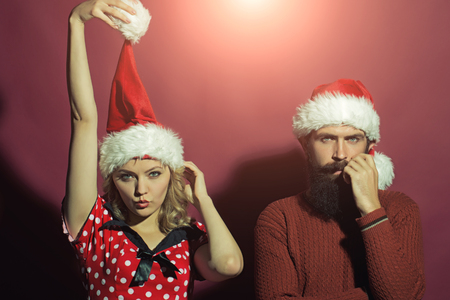man long hair: New year funny couple of blond woman with curly hair and man with long beard in red santa claus hat celebrating christmas standing on studio purple background, horizontal picture Stock Photo