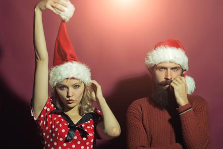 Nieuwe jaar grappige paar blonde vrouw met krullend haar en man met een lange baard in de rode hoed van de Kerstman viert kerst staande op studio paarse achtergrond, horizontaal beeld