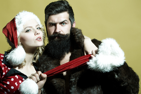 beard woman: New year young funny couple of blond woman with curly hair in dress and man with long beard in red santa claus hat and fur coat celebrating christmas standing on studio yellow background, horizontal Stock Photo