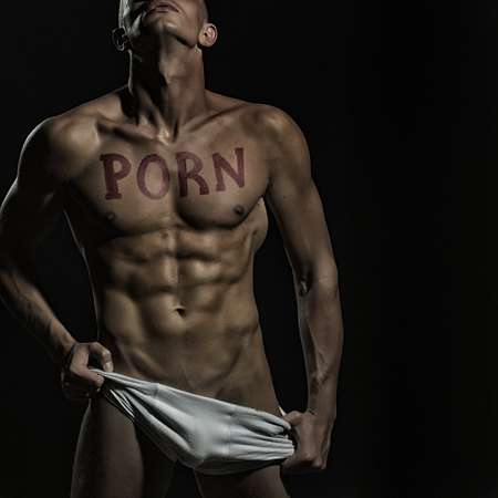 breasts erotic: One handsome undressed muscular man in white underwear with beautiful sexy body with text of porn written by red lipstick standing with trown back head in studio on black background, square picture Stock Photo