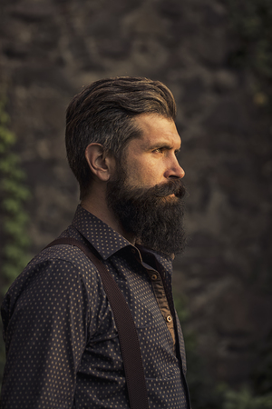 Closeup side view of one handsome senior man with black hair and long lush beard in blue shirt and purple trausers standing outdoor on stone wall grey background, vertical picture