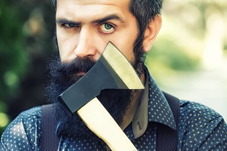 logger: Portrait of one strong stylish male logger of young serious man with long lush black beard and moustache in shirt holding wooden axe standing sunny day outdoor on natural background, horizontal