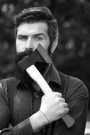 logger: Portrait of one handsome strong stylish male logger of young serious man with long lush beard and moustache in shirt holding wooden axe standing outdoor on natural background black and white, vertical Stock Photo