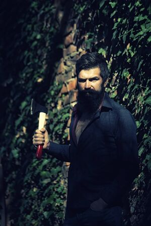 logger: One handsome strong stylish male logger of young man with long lush black beard and moustache in shirt holding wooden axe standing near brick wall outdoor, vertical picture