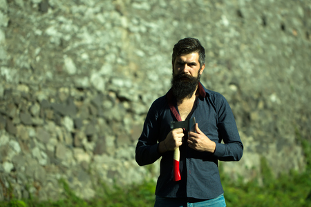 stone cutter: One handsome strong stylish male logger of young man with long lush black beard and moustache in shirt holding wooden axe standing near grey stone wall outdoor, horizontal picture Stock Photo