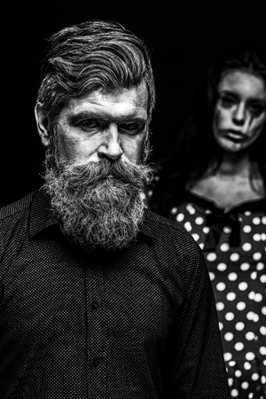 immortal: Closeup view of couple of painted halloween holy chrackters woman and man with long lush beard looking forward on studio wall background black and white, vertical picture