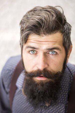 volto uomo: Vista Ritratto di un bel anziano uomo alla moda con i capelli neri e la barba lunga lussureggiante in camicia blu in piedi all'aperto su sfondo bianco muro guardare avanti, immagine verticale