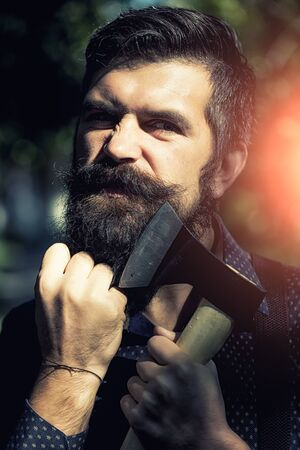 logger: Portrait of one handsome strong stylish male logger of young serious man with long lush black beard and moustache in shirt holding wooden axe standing sunny day outdoor on natural background, vertical