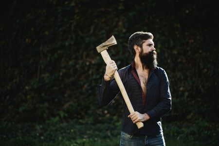 logger: One handsome strong stylish male logger of young man with long lush black beard and moustache in shirt holding wooden axe standing near wall with climber plant outdoor, horizontal picture Stock Photo