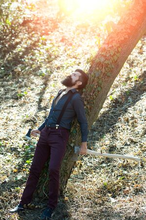 logger: One handsome strong stylish male logger of young man with long lush black beard and moustache in shirt holding wooden axe lying on tree outdoor on natural background, vertical picture Stock Photo