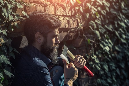 logger: One handsome strong stylish male logger of young man with long lush black beard and moustache in shirt holding wooden axe standing near brick wall outdoor, horizontal picture