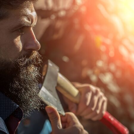 logger: One handsome strong stylish male logger of young man with long lush black beard and moustache in shirt holding wooden axe standing in forest outdoor on natural background, square picture Stock Photo