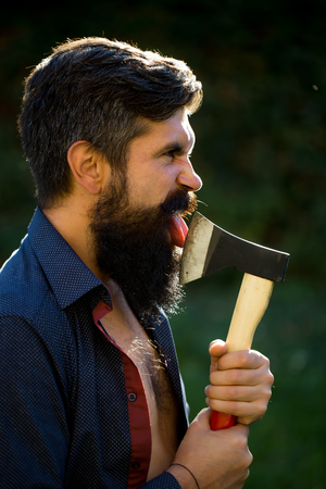 logger: Side view of one handsome strong stylish male logger of young man with long lush black beard and moustache in shirt holding wooden axe standing near wall with climber plant outdoor, vertical picture
