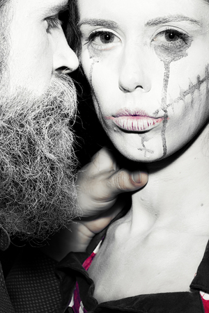 pranks: Closeup view of couple of painted halloween holy chrackters woman and man with long lush beard looking forward on studio wall background black and white, vertical picture