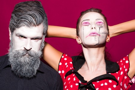 immortal: Closeup view of couple of painted halloween holy chrackters woman in red dress with lips eyes and man with long lush beard looking forward on studio purple wall background, horizontal picture