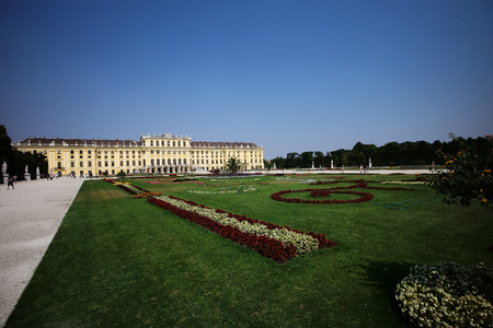 showplace: Beautiful schonbrunn medieval baroque palace imperial residence of habsburg dynasty old historical showplace yellow-colored building with green grass garden outdoor on blue sky background, horizontal Editorial