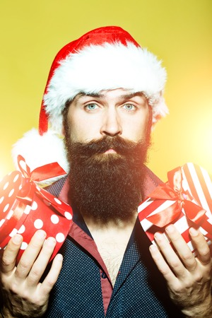 Portrait of one senior new year man with long black beard in shirt and red santa claus hat holding two wrapped present boxes in hands for christmas standing in studio on yellow background, vertical 版權商用圖片