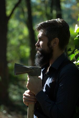 logger: One handsome strong stylish male logger of young man with long lush black beard and moustache in shirt holding wooden axe standing in forest outdoor on natural background, vertical picture