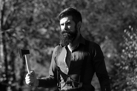 logger: One handsome strong stylish male logger of young man with long lush beard and moustache in shirt holding wooden axe standing in forest outdoor on natural background black and white, horizontal picture Stock Photo