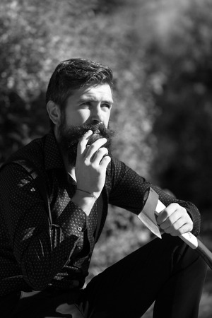 logger: One strong male logger of young man with long lush beard and moustache in shirt holding wooden axe sitting in forest smoking cigarette outdoor on natural background black and white, vertical picture