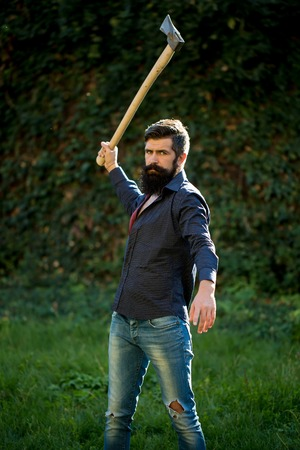 axe: One handsome strong stylish male logger of young man with long lush black beard and moustache in shirt holding wooden axe standing near wall with climber plant outdoor, vertical picture Stock Photo