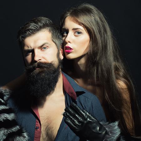 seni: Bella ed elegante giovane coppia sensuale della donna in maniche di pelliccia e guanti abbraccia l'uomo con la barba lunga lussureggiante in camicia con torso nudo seduto in studio su sfondo nero, immagine quadrata