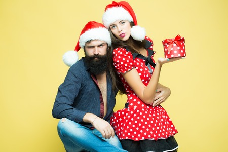 Beautiful cute young funny couple of new year man with long black beard and woman in red dress and santa hat holding gift box for christmas standing in studio on yellow background, horizontal picture