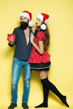 Beautiful cute young funny couple of new year man with long black beard and woman in red dress and santa hat holding gift box for christmas standing in studio on yellow background, vertical picture Archivio Fotografico