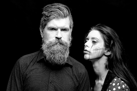 pranks: Closeup view of couple of painted halloween holy chrackters woman and man with long lush beard looking forward on studio wall background black and white, horizontal picture Stock Photo