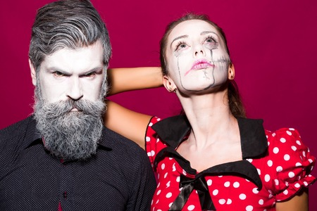 pranks: Closeup view of couple of painted halloween holy chrackters woman in red dress and man with long lush beard looking forward on studio purple wall background, horizontal picture