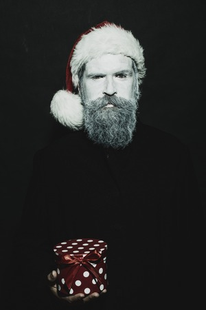 white beard: Closeup portrait of one senior frozen new year man with painted face in white and long beard in christmas santa red hat holding present box in studio on black background, vertical picture