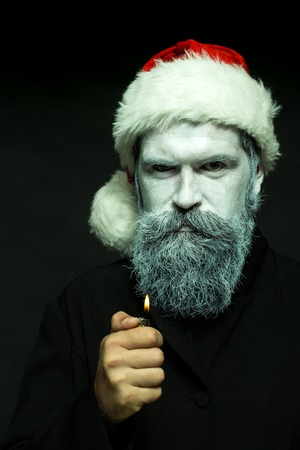 adult  male: Closeup portrait of one senior frozen new year man with painted face in white and long beard in christmas santa red hat holding cigarette lighter in studio on black background, vertical picture