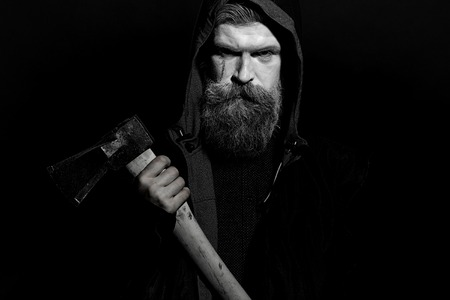 hunter man: Portrait closeup view of one senior hunter man in hood with spooky painted face of zombi and long white lush beard holding axe black and white, horizontal picture Stock Photo