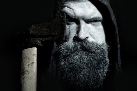 Portrait closeup view of one senior hunter man in hood with spooky painted face of zombi and long white lush beard holding axe black and white, horizontal picture Stock Photo