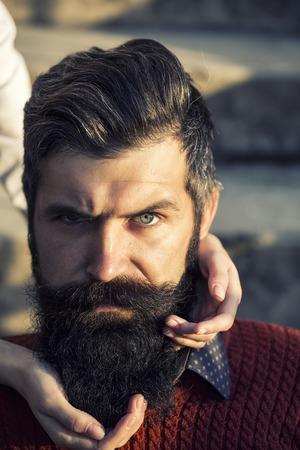 modelos hombres: Retrato del primer de un hombre mayor serio guapo con barba larga negro en el su�ter rojo que mira hacia adelante y las manos femeninas que tocan la cara d�a soleado al aire libre en el fondo natural, imagen vertical Foto de archivo