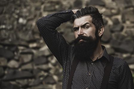 bigote: Primer punto de vista de un hombre mayor hermoso con el pelo negro largo y la barba frondosa en camisa azul y púrpura trausers de pie al aire libre en la pared de piedra fondo gris, horizontal de la imagen