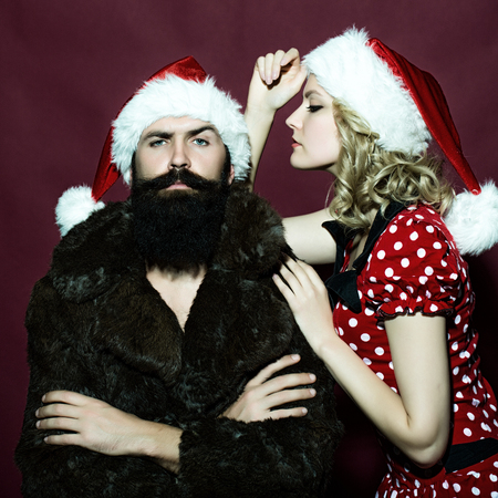 New year young couple of blond woman with curly hair in dress and man with long beard in red santa claus hat and fur coat celebrating christmas standing on studio purple background, square photo