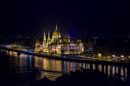 Beautiful amazing hungarian parliament made in neo-gothic architecture illuminated with multi-colored lights standing on danube with reflection on water at night in budapest hungary europe, horizontal