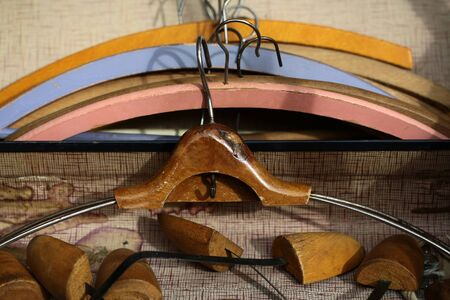 brass rod: Closeup boot trees and varnish retro wooden coat hanger against lots of vintage clothing hangers angular frames made of timber  painted coloured tired aged background, horizontal picture